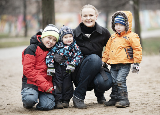Happy mother with her three young children