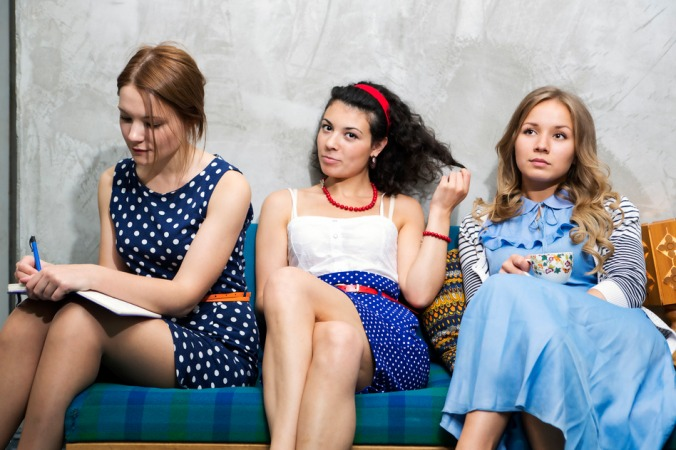 Womans in different dresses sit on sofa